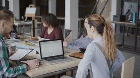 Den kvinnliga lagledaren kommer med dokument till det idérika affärslaget Grupp människormöte för blandat lopp i modernt kontor lager videofilmer