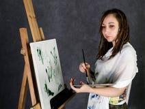 Den kvinnliga målarfärgkonstnären som poserar bredvid en staffli och målarfärger på en kanfas, visar en drömmeri royaltyfria bilder