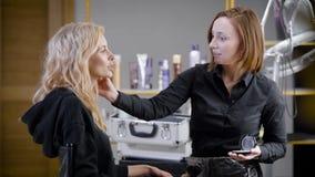 Den kvinnliga makeupkonstnären täcker framsidan av den unga blonda kvinnan vid kosmetiskt pulver, genom att använda borsten, i sk stock video