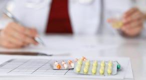 Den kvinnliga medicindoktorn fyller upp receptformen till den tålmodiga closeupen Universalmedel och liv sparar, ordinerar behand Royaltyfria Bilder