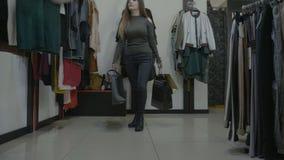 Den kvinnliga modellen går i ett lager med höga häl och rymmer hennes telefon i jeansbakfickan, medan söka efter ny kläder - arkivfilmer