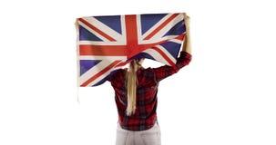 Den kvinnliga modellen står tillbaka och lyfter den engelska flaggan på vit bakgrund arkivfilmer