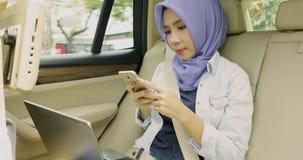 Den kvinnliga muslimen använder smartphonen i bil arkivfilmer
