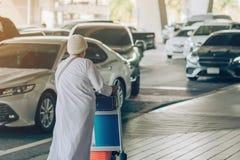 Den kvinnliga passageraren med stort rullbagage går för att vänta på bilen för att välja upp fotografering för bildbyråer