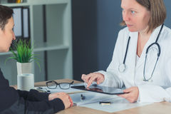 Den kvinnliga patienten konsulterade vid doktorn i sjukhuskontor royaltyfri foto