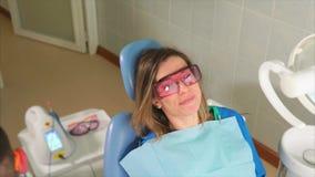Den kvinnliga patienten med den skyddande apelsinen rullar med ögonen sammanträde på den tand- soffan stock video