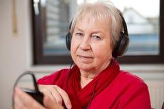 Den kvinnliga pensionären är lyssnar musik royaltyfri foto