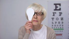 Den kvinnliga pensionären i exponeringsglas som stänger ögat och skakar huvudet, ålder gällde sjukdomar stock video