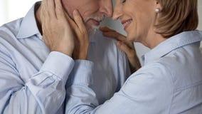 Den kvinnliga pensionären som kuper den manliga kinden, man att kyssa hennes hand, harmoniskt familjeliv fotografering för bildbyråer