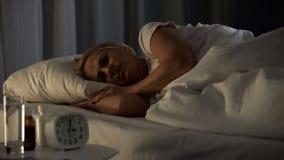 Den kvinnliga pensionären som sover i säng, vårdhemlivsstilen, pensionärnatt, vilar royaltyfria foton