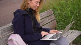 Den kvinnliga personen som pratar i samkväm, knyter kontakt, genom bärbara datorn och att sitta på bänk nära grönt gräs lager videofilmer