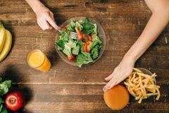 Den kvinnliga personen väljer sund organisk mat arkivfoto