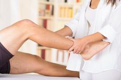 Den kvinnliga physio terapeuten räcker arbete på manliga patienter lågt lägger benen på ryggen och ankeln, oskarp klinikbakgrund royaltyfri fotografi