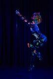 Den kvinnliga poldansaren i ljust neon färgar under ultraviolet Royaltyfri Bild