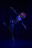 Den kvinnliga poldansaren i ljust neon färgar under ultraviolet Arkivfoton