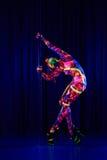 Den kvinnliga poldansaren i ljust neon färgar under ultraviolet Royaltyfri Foto