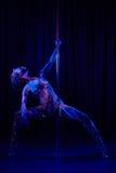 Den kvinnliga poldansaren i ljust neon färgar under ultraviolet Fotografering för Bildbyråer