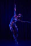 Den kvinnliga poldansaren i ljust neon färgar under ultraviolet Royaltyfria Bilder