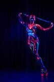 Den kvinnliga poldansaren i ljust neon färgar under ultraviolet Arkivbilder