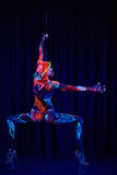 Den kvinnliga poldansaren i ljust neon färgar under ultraviolet Arkivfoto