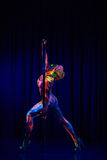 Den kvinnliga poldansaren i ljust neon färgar under ultraviolet Arkivbild