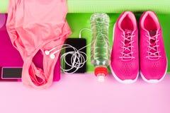 Den kvinnliga rosa färguppsättningen av saker och tillbehör för att spela sportar ligger på en matt gräsplan arkivbilder