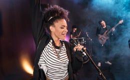 Den kvinnliga sångaren med mikrofonen och vaggar - och - rullar musikbandet som att utföra som är hårt, vaggar musik royaltyfria bilder