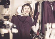 Den kvinnliga shopparen som undersöker långa muffskjortor i underkläder, shoppar Royaltyfri Fotografi