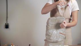 Den kvinnliga skulptören klipper det stora stycket av våt lera vid metalltråd i studio arkivfilmer