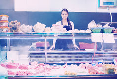 Den kvinnliga slaktaren med späcker och kött i lager Arkivfoton