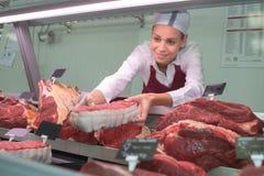 Den kvinnliga slaktaren med späcker och kött i räknarelager Arkivbilder