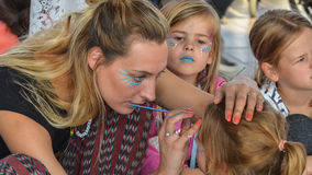 Den kvinnliga sminkkonstnären målar framsidan av en ung flicka (Zandvoort, Noordholland, Nederländerna - ca Oktober 2015) arkivfoton