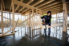 Den kvinnliga snickareCutting Wood With handen såg i ofullständiga Buildi Arkivfoton