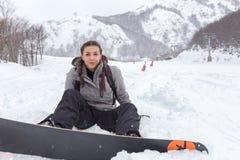 Den kvinnliga snowboarderen med flätade trådar placeras på den nya snöig groen Royaltyfri Foto