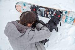 Den kvinnliga snowboarderen söker material inom ryggsäcken Royaltyfri Fotografi