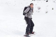 Den kvinnliga snowboarderen skidar Arkivfoton