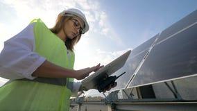Den kvinnliga sol- teknikern i exponeringsglas arbetar med hennes datoranseende bredvid en solpanel arkivfilmer