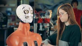 Den kvinnliga specialisten kontrollerar hur en cyborg rullar dess ögon stock video