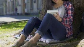 Den kvinnliga studenten fokuserade på kunskap och tankar som skriver essäen i anteckningsbok stock video