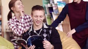 Den kvinnliga studenten kommer upp till hennes vänner som tillsammans ger en tumme till och med boken lager videofilmer