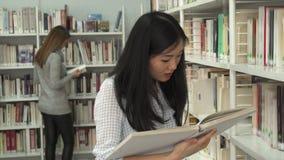 Den kvinnliga studenten läser boken på arkivet lager videofilmer