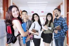 Den kvinnliga studenten möter hennes nya vänner royaltyfri foto