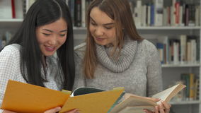 Den kvinnliga studenten pekar hennes pekfinger in i boken på arkivet stock video