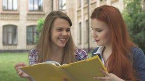 Den kvinnliga studenten pekar hennes pekfinger in i tidskriften utomhus royaltyfri foto