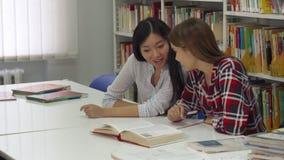 Den kvinnliga studenten sitter ner nära hennes klasskompis på arkivet royaltyfria foton