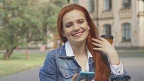 Den kvinnliga studenten skrattar på vad hon ser på hennes smartphone på universitetsområde royaltyfria foton