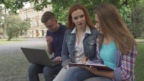 Den kvinnliga studenten skriver i hennes skrivbok på universitetsområde royaltyfri foto