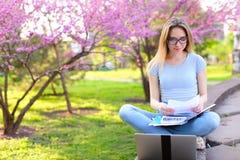 Den kvinnliga studenten som studerar med bärbara datorn, och legitimationshandlingar, i att blomma, parkerar fotografering för bildbyråer