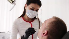 Den kvinnliga tandläkaren i maskering undersöker det muntliga hålet av patienten Mannen sitter i den tand- stolen, tandvård arkivfilmer