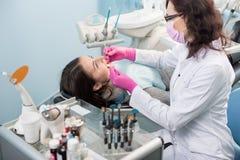 Den kvinnliga tandläkaren med tand- hjälpmedel - avspegla och sondera behandling av tålmodiga tänder på det tand- klinikkontoret  royaltyfri bild